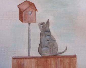 Cat staring at birdhouse