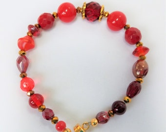 "Red bead bracelet,8"" Mixed beads, Clear,opaque,glass,acrylic,marbled,w copper colored faceted crystal and gold spacers, and magnetic closure"