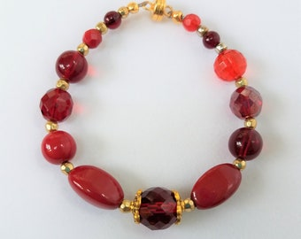 "Red bead bracelet,7.5"" Mixed bead,opaque,glass,acrylic,marbled,w copper colored faceted crystal and gold spacers, and magnetic closure"