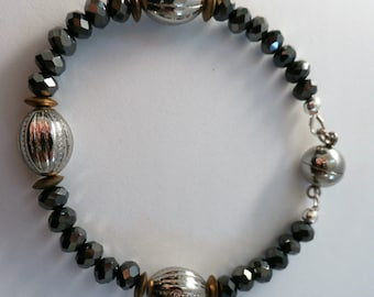 Charcoal faceted crystal bracelet,silver beads, gold discs,gray magnet closure,hand wired w/ jewelers wire,strong magnet,matches collection