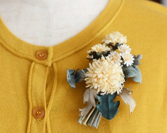 A flower corsage with dandelions and mini Daisy