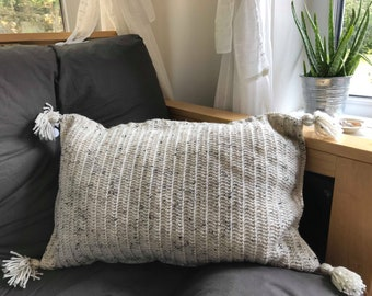 large cream aran wool cushion with tassel and button details