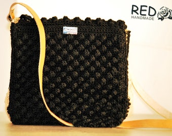 Handmade knitted handbag with genuine leather round her drawn newspaper and leather handle straight.