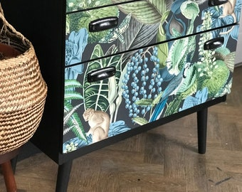Vintage Schreiber chest of drawers refinished in a black frame and tropical blue and green jungle print drawer fronts.