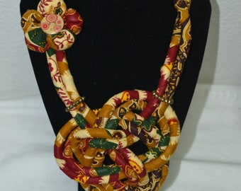 string necklaces in African cloth with finishes on lined buttons and pogo flowers