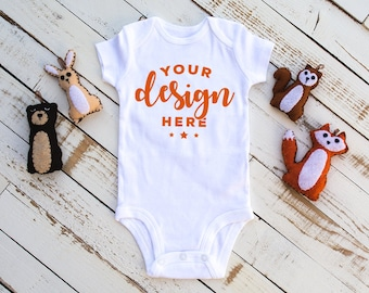 Download Free White Bodysuit Mock-up With Felt Woodland Animals On Distressed Wood Background Infant Mock T-shirt Mock-up Commercial Template PSD Template