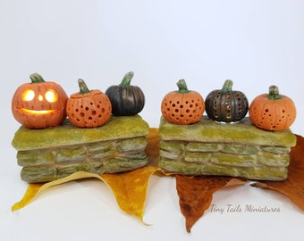 Pumpkins, three light up miniature pumpkins on a wall.