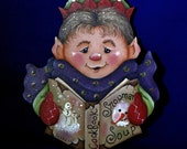 Hand painted Elf Christmas ornament, reading his snowman soup cookbook, hand painted in acrylic on wood, 5 by 4 inches, ribbon hanger