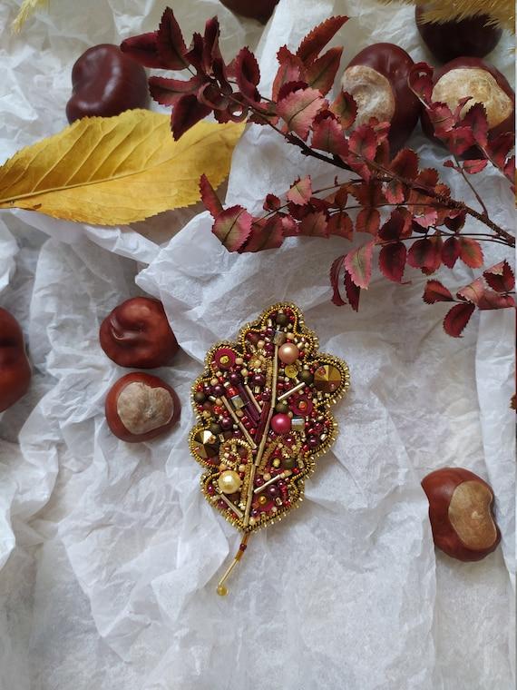 Gold and red beaded brooch oak leaf. Handwork.