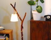 A wooden floor lamp with a cream shade, a wooden lamp, a romantic floor lamp, a branch floor