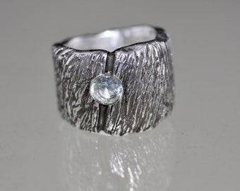 Striking wide statement ring with great 925 silver surface structure and a blue spinel