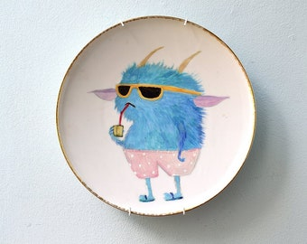 Vintage wall plate hand-painted with porcelain paint. With a cool blue summer monster