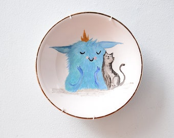 Porcelain wall plate hand-painted with cute royal monsters and a cat