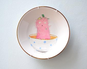 Wall plate with a hand-painted pink monster in the soup bowl
