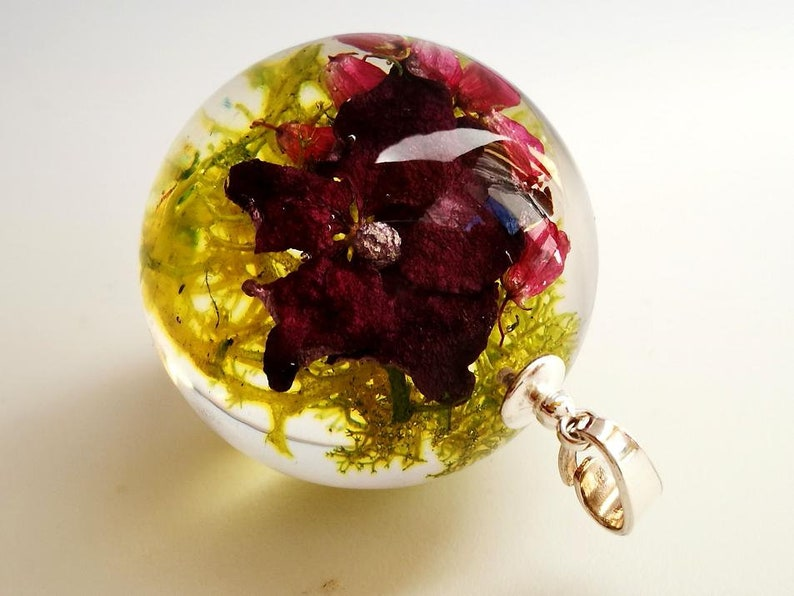 Growths and pink hydrangea necklace in sphere from resin composition in resin