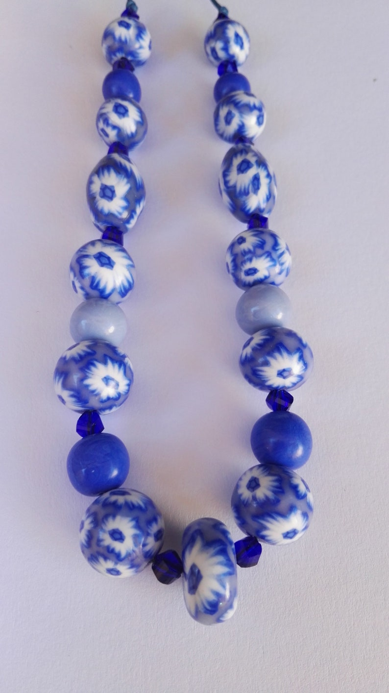 Fimo Polymer paste pearl necklace with blue and white celestial flowers on waxed lanyard