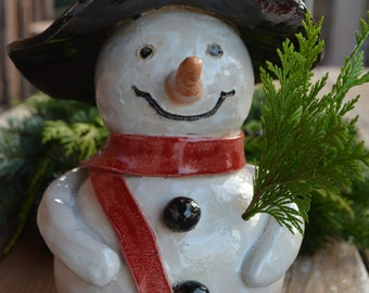 Snowman with red scarf made of clay