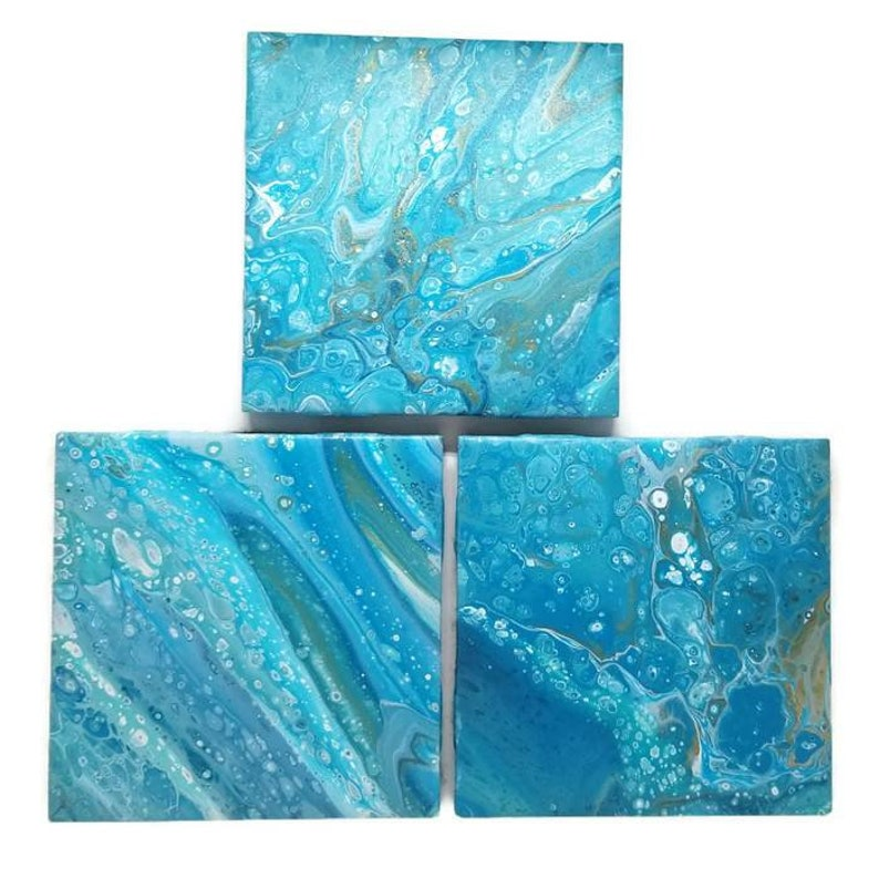 hand painted ceramic tile coasters painted using acrylic poured paint  method sealed with epoxy resin finish / fluid art coaster tiles