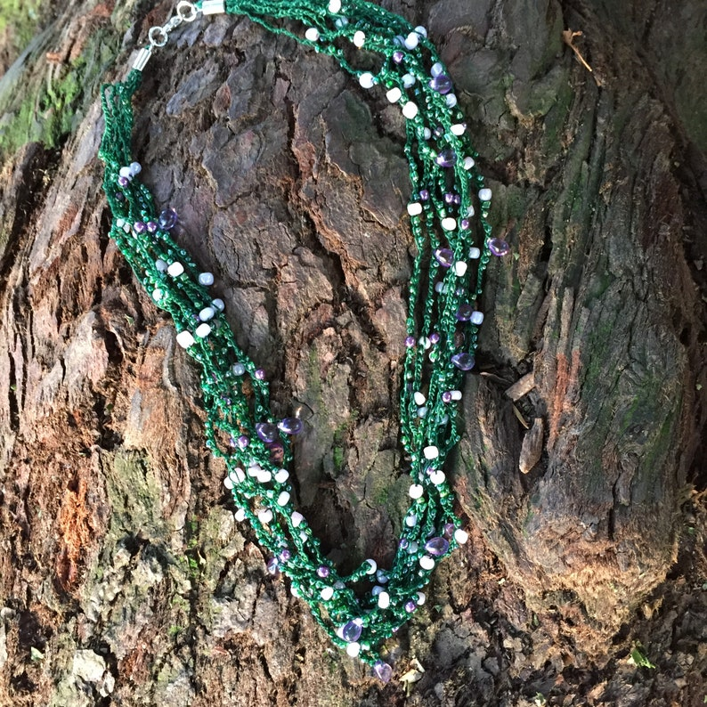 crocheted jewelry necklace with green thread and violet seed and glass beads