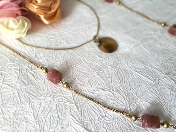 Collar with shiny pendant encrusted with a green stone mounted on a thin gold metal chain