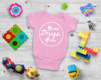 Download Free Blank Pink Baby Onesie Mockup, Fashion Design Styled, Baby Mock up with Toys - Flat, Direct View on Wood Background - JPG Download PSD Template
