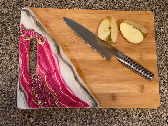 Hand poured resin bamboo cheese/cutting board in marble fuchsia,white, and gold glitter accented with acrylic gems 15x11.5 trimmed in gold