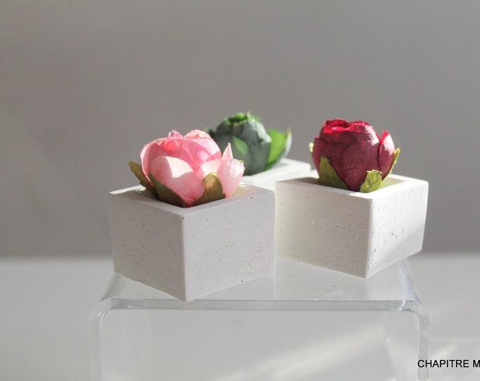 Trio of roses on white concrete base
