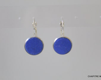 Silver earrings and blue concrete