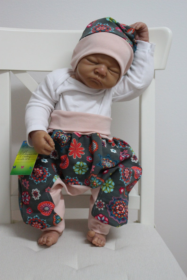 75a1ada7cd352 Set: Baby pump trousers with cap-pink floral pattern