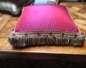 Ruby red faux silk cushion with long fringe
