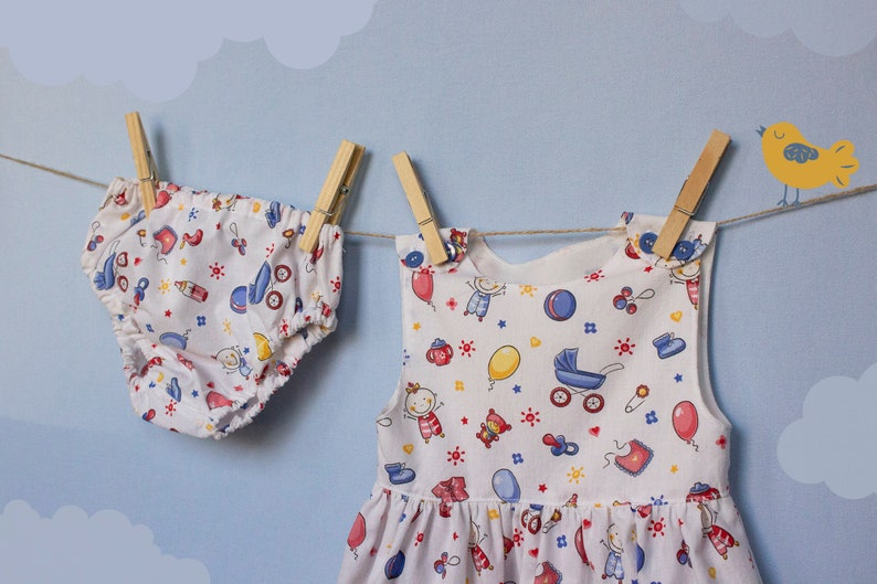 Baby girl pinafore in toys and balloons print Overall dress image 0