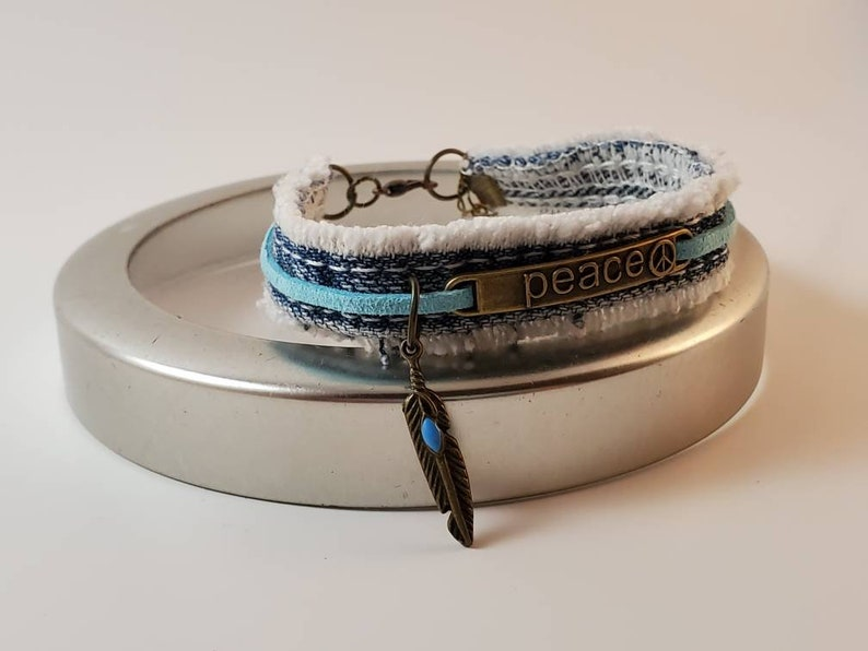 Fringed blue denim bracelet with bronze PEACE center and feather charm with aqua stone