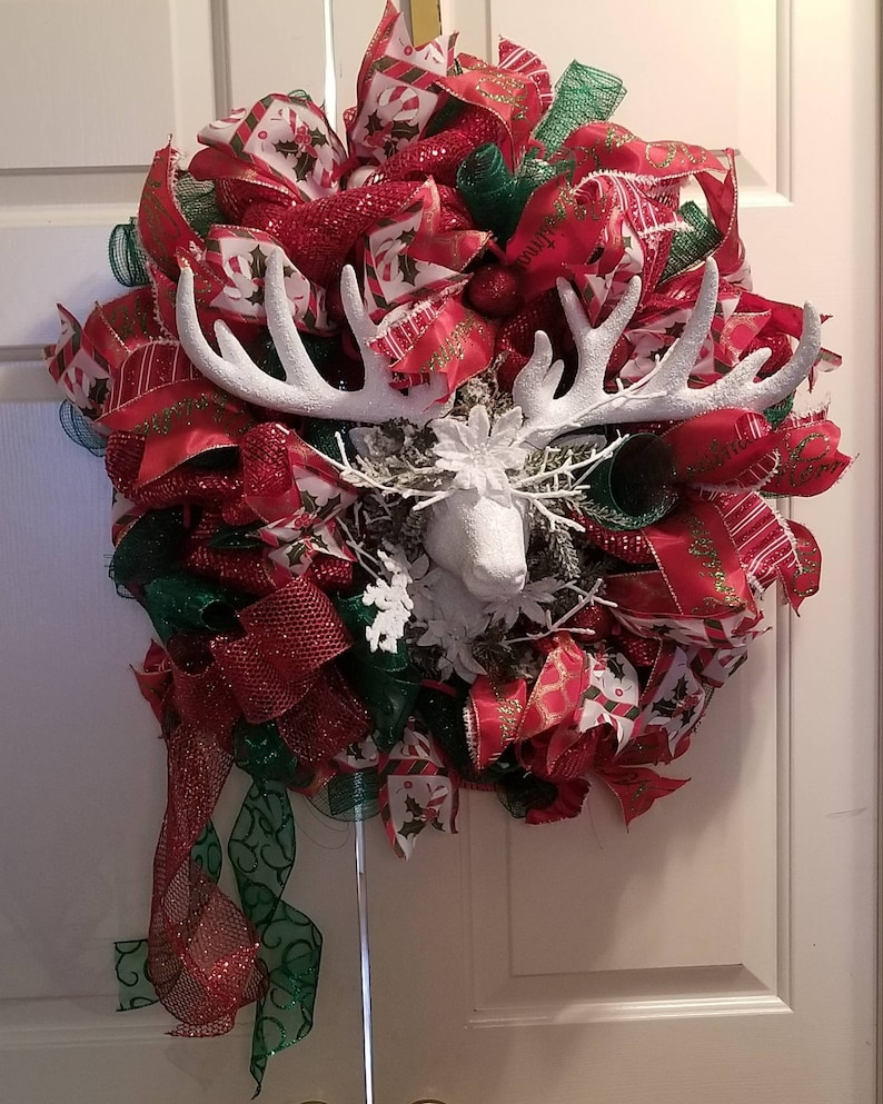 Large red and green wreath with a snow white deer in the center.