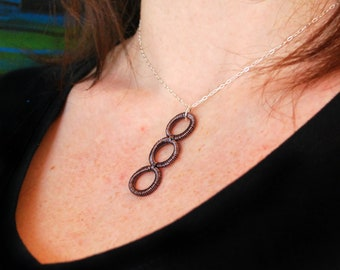 Hand coiled wire pendant - warm charcoal colour