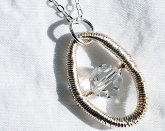Hand coiled wire pendant with Swarovski crystal - bright silver colour