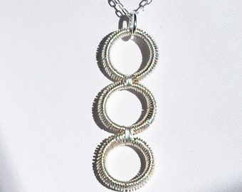 Hand coiled wire pendant - silver colour