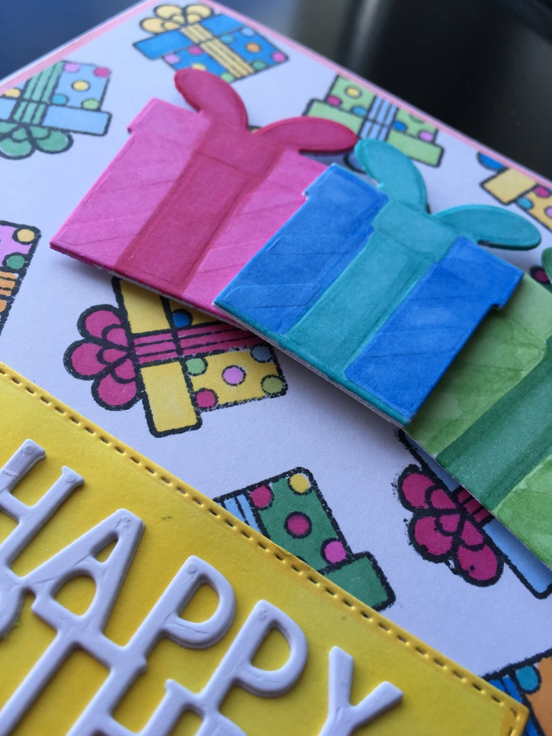 Happy birthday card with three dimensional presents laid on a stamped and coloured presents background