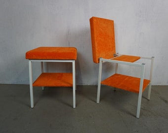 Two bright folding stools in orange