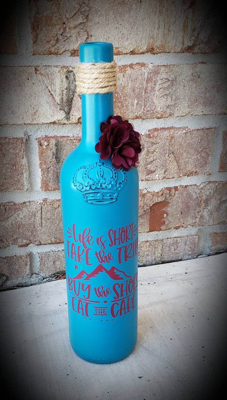 Custom painted wine bottle decor made from repurposed bottles perfect for wedding decor.