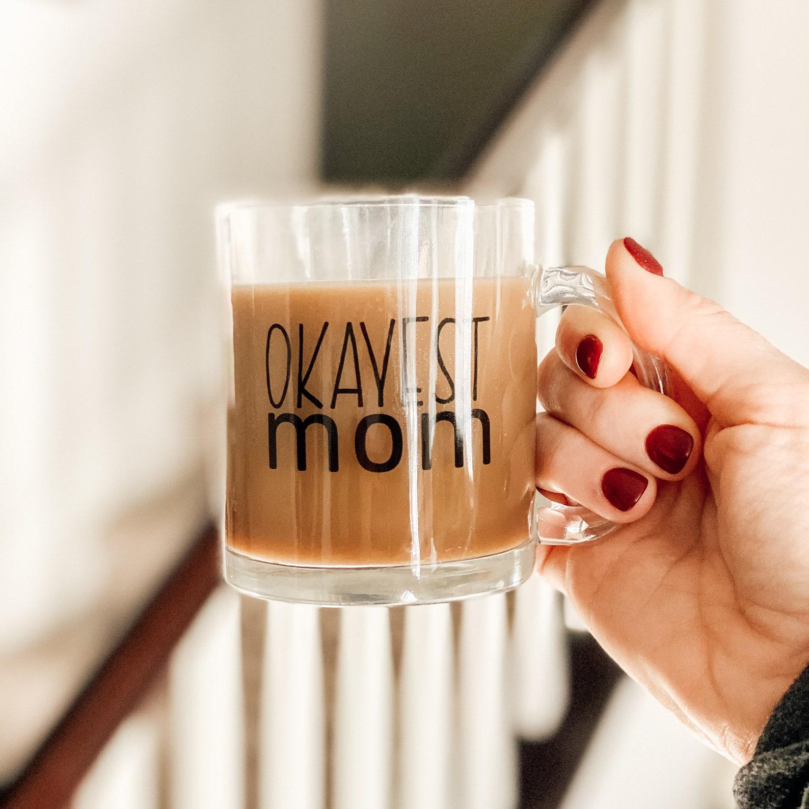 okayest mom glass mug with coffee and hand holding
