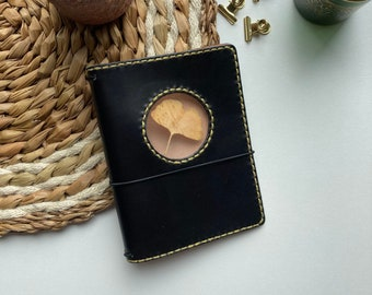 Black a6 see through journal cover with gold stitching and a dried Gingko leaf