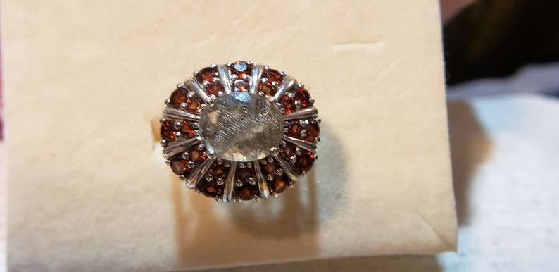 Centeral oval rutilated quartz surrounded by smaller and larger garnets in inner and outer stones Size 7. Platinum over sterling silver