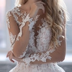 Tulle wedding dress Urika with flowers lace makes a beautiful thin waist, long lace sleeves Back with Buttons and soft tulle skirt.