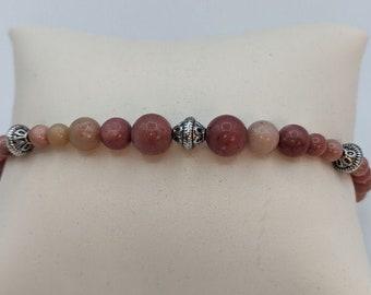 This beautiful semi precious Rhodonite Bracelet has pewter pacer beads.