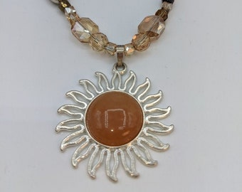 A beautiful Sun Pendant rest upon the hand beaded necklace w/ glass and pewter beads.