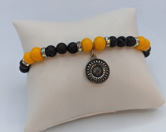 Charming bracelet w/ black volcanic beads and yellow ceramic beads with a pewter sunflower charm.