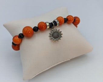 Charming bracelet w/  a pewter sunflower charm and acrylic beads on a stretchy cord.