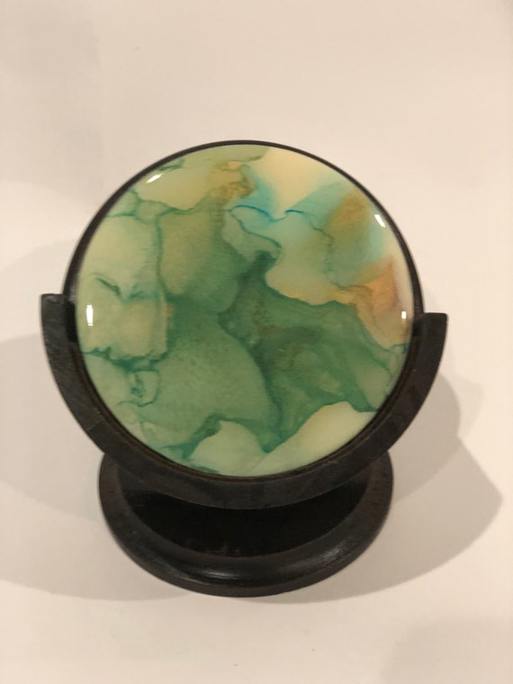 Set of 5 unique green hand painted alcohol ink and resin on wood coasters with mahogany wood stand.
