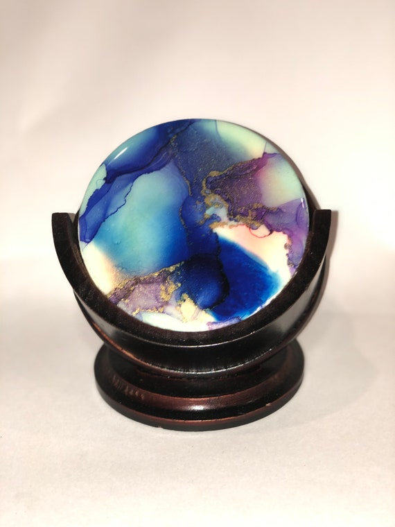 Set of 5 unique blue, purple, gold, red and white hand painted alcohol ink and resin on wood coasters with mahogany wood stand.