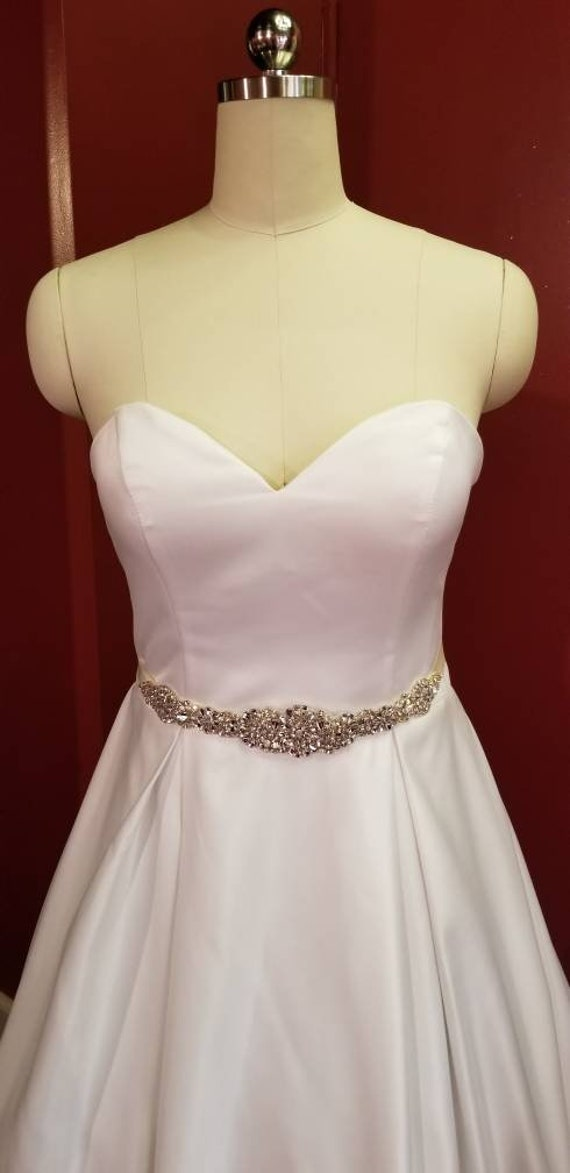 wedding gown with sweetheart neckline, ballgown, box pleated skirt, cathedral train and beaded sash.